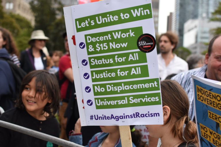 Protest sign saying let's unite to win