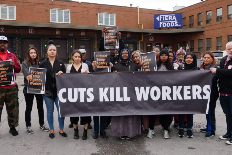 People outside of Fiera foods holding banner that reads Cuts Kill Workers