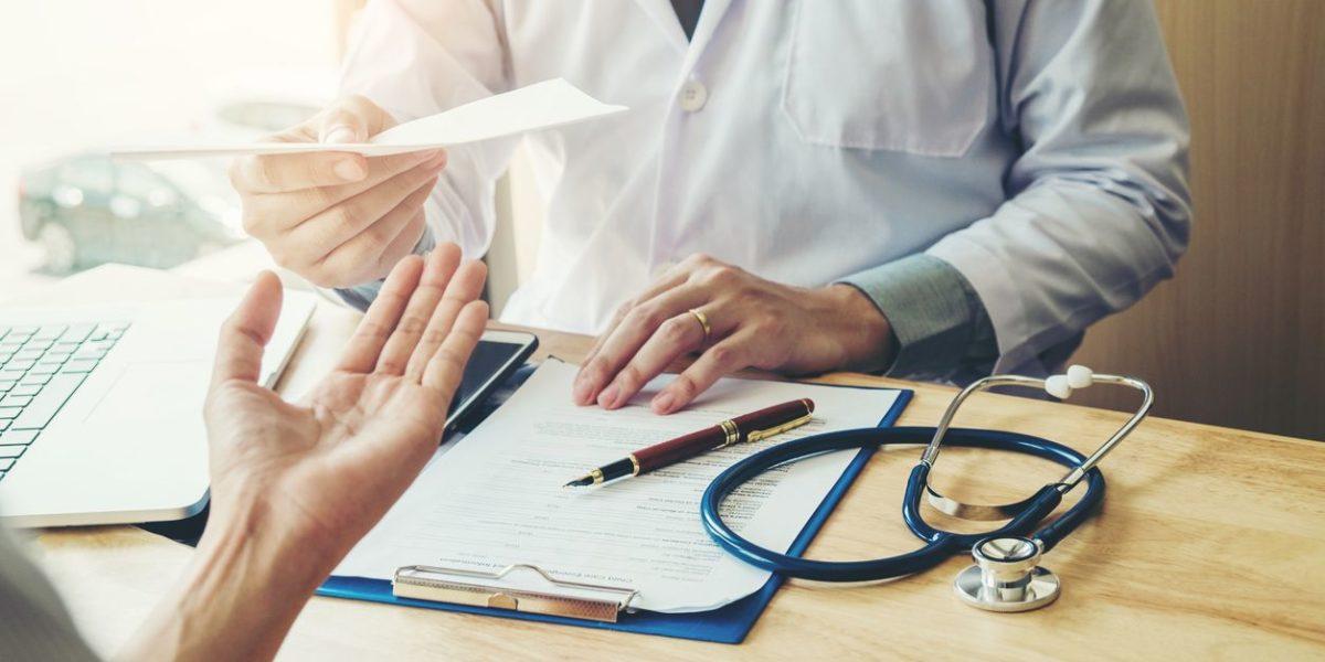 Doctor handing a person a perscription