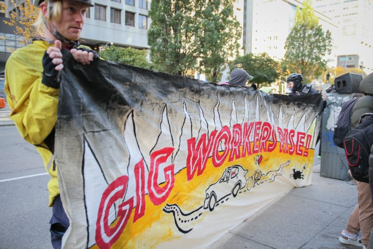 Bicycle couriers holding a banner that reads Gig workers rise